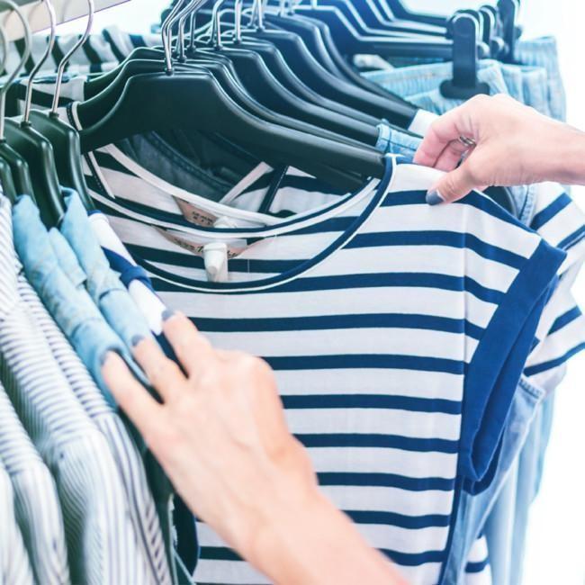 Valokuva, jossa kädet selaavat vaaterekillä roikkuvia paitoja ja puseroita